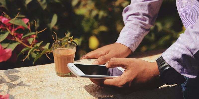 Man checking phone with a tropical drink.